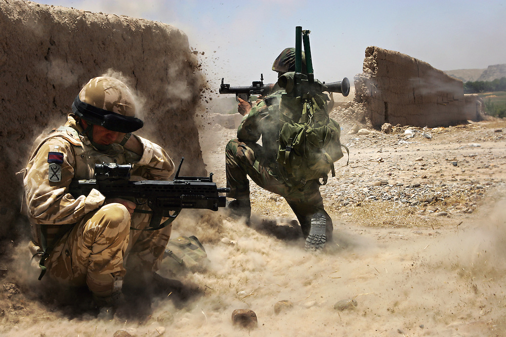 A British Army officer mentoring Afghan forces crouches behind a mud wall and covers one ear as an Afghan National Army soldier fires an RPG (Rocket Propelled Grenade) at a Taliban position. Kajaki, Helmand Province, Afghanistan on the 7th of July 2007.