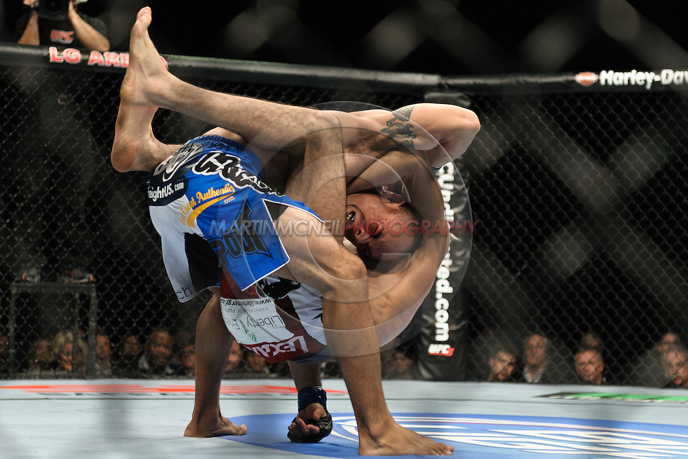 """BIRMINGHAM, ENGLAND, NOVEMBER 5, 2012: Edward Faaloloto (facing) is caught in a guillotine choke by Terry Etim during """"UFC 138: Munoz vs. Leben"""" inside the National Indoor Arena in Birmingham, United Kingdom"""
