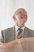 Senior man in spectacles reading newspaper half length