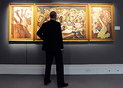 © licensed to London News Pictures. LONDON, UK.  10/06/11. A man looks at 'Cutting the Cloth (The Hat Stand, The Anthracite Stove, Cutting The Cloth)' by Stanley Spencer Estimated £1,500,000 - 2,500,000. Preview of Sotheby's upcoming Evill/Frost Collection Sale. Highlights from the collection of 20th century British art include an early work by Lucian Freud, bought for £18 in 1944, and now estimated at £400,000 to £600,000, a Henry Moore sculpture of a mother and child in a rocking chair that was designed as a moving toy for his daughter, estimated at £800,000 to £1.2 million and Stanley Spencer's Workmen in the House, estimated at £1.5 £2.5 million. The auctions take place on June 15 and 16.. Photo credit should read Stephen Simpson/LNP