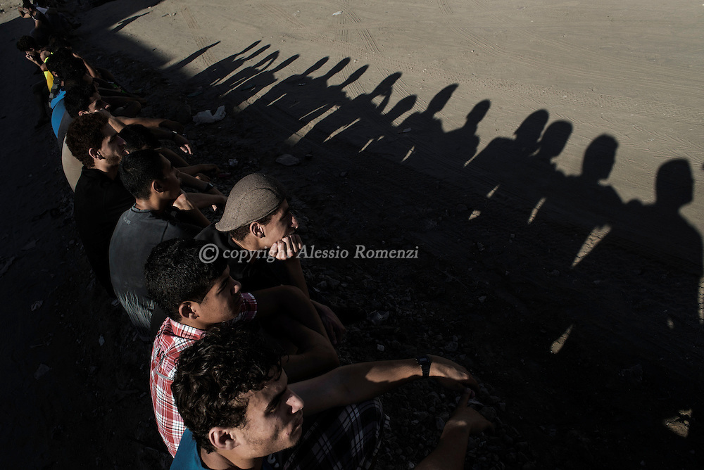 Gaza Strip, Gaza City: Palestinian wait outside the mosque where people pray over the bodies of four boys, all from the Bakr family, killed by Israeli naval bombardment, on July 16, 2014. ALESSIO ROMENZI