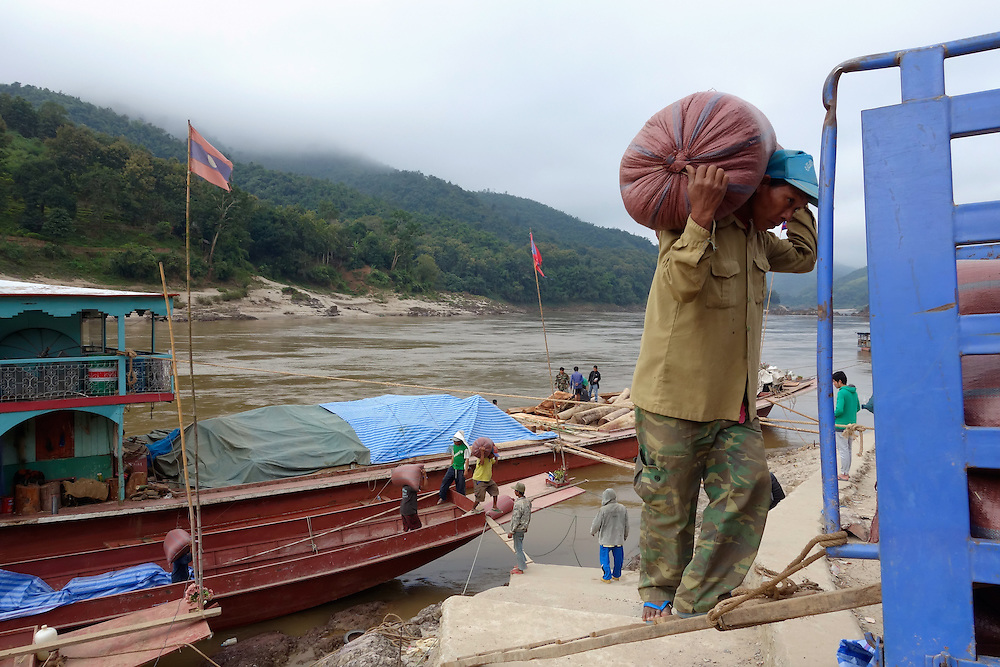 Workers carrying heavy sacks of rainforest product from a cargo boat on the Mekong River to a truck in Pakbeng, Laos.