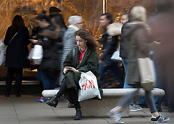 © Licensed to London News Pictures. 23/12/2016. London, UK. A shopper takes a break as others look for last minute bargains in Oxford Street on the last working day before Christmas. Photo credit: Peter Macdiarmid/LNP