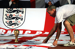 With a replica World Cup trophy on the running track in The Central Stadium in Almaty, Kazakhstan an England fan adjusts the flags out on display