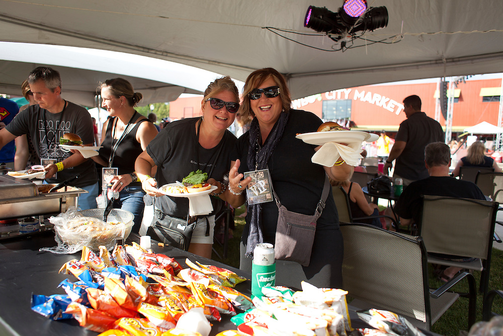 Debbie Peffly of St. Louis, Missouri and her friend Susan Anderson of North Liberty take advantage of a break in the music to have some dinner in the VIP area of the NewBo Music Fest in downtown Cedar Rapids on Saturday, August 8, 2015. The two are fans of Young the Giant and Anderson has seen the band perform three other times in various corners of the United States. (Rebecca F. Miller/Freelance for the Gazette)