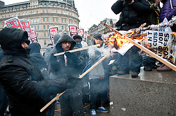 © under license to London News Pictures. 30/11/2010. Students demonstrate in London against the raising of tuition fees for the third time. Pictured are students burning banners at Trafalgar Square.  Credit should read Michael Graae/London News Pictures