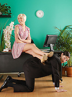 Female office worker resting legs on man kneeling on hands and knees in office portrait