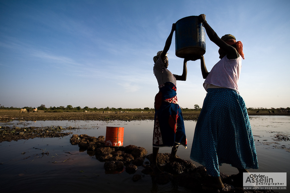 A woman helps another lift a bucket of water on top of her head at the Dikunani dam in Savelugu, northern Ghana, on Friday March 9, 2007. The only of four water sources that has not completely dried out around Savelugu, the pond is used by hundreds of people daily who sometimes walk several kilometers to fetch water. Despite the presence of mesh filters available to people who come get water, cases of guinea worm in the area have gone up sharply in the recent months.