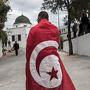 Tunisi, un ragazzo al cimitero di Tunisi vicino alla tomba di Chokri Belaid indossa la bandiera della Tunisia.