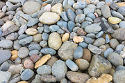 Pastel shades and various sizes of granite rocks and pebbles on beach on Isle of Skye, the Western Isles of Scotland, UK