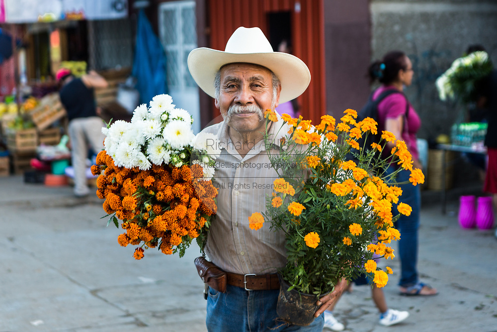 An elderly Mexican man carries bundles of flowers to the gravesite of his wife for Day of the Dead festival known in Spanish as Día de Muertos at the old cemetery October 31, 2013 in Xoxocotlan, Mexico. The festival celebrates the lives of those that died.