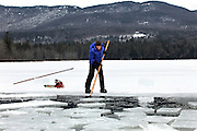 Jane Kellogg of Campton pushes blocks during the second day of the ice Harvest on Squaw Cove, Squam Lake in Sandwich, NH. The ice is used for refrigeration by Rockywold and Deep Haven Camps and by others who have ice houses in the area.