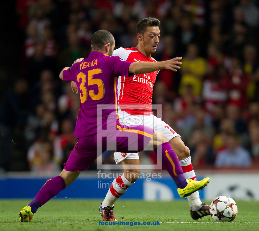 Mesut Ozil of Arsenal and Yekta Kurtulus of Galatasaray during the UEFA Champions League match at the Emirates Stadium, London<br /> Picture by John Rainford/Focus Images Ltd +44 7506 538356<br /> 01/10/2014