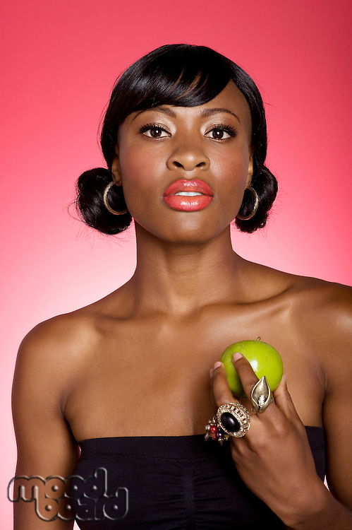 Portrait of young woman holding green apple over colored background