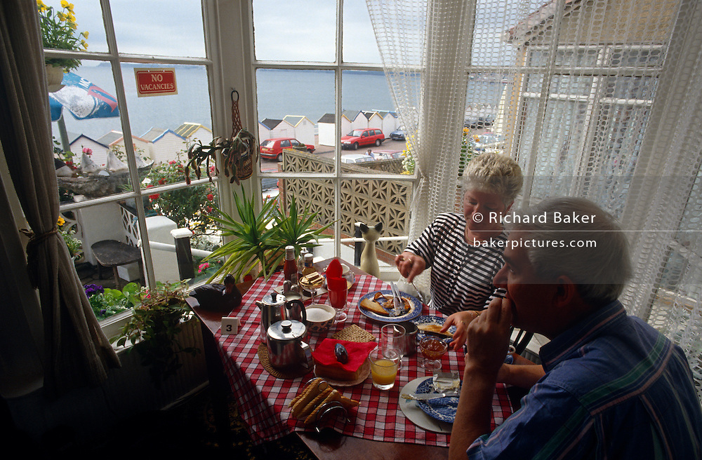 On table 3, a holiday couple enjoy a full English cooked breakfast in the bay window of a Bed & Breakfast (B+B) in the Devon seaside resort of Paignton. Seated in the bright area that overlooks the seafront, beach huts and the calm sea in the distance. On the gingham tablecloth is a traditional English tea pot, toast rack and jam and they tuck into slices of white bread toast accompanied by orange juice. A No Vacancies sign hangs in the window for potential guests to spot as they walk the promenade.