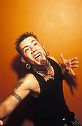 Man posing for camera in a club, with goatee and piercings, skull tattoos, UK 2000's,