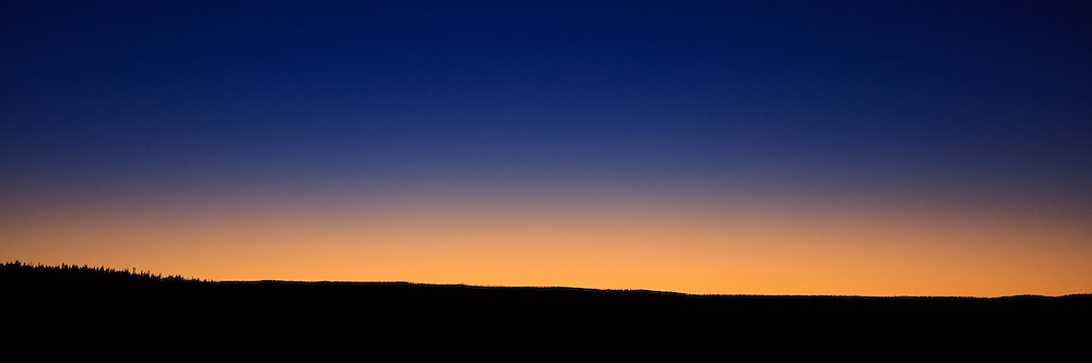 The last light of sunset creates an orange glow behind a tree-lined ridge in Yellowstone National Park.