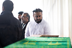 © Licensed to London News Pictures . 12/05/2017 . Manchester , UK . A family member looks through the window in the top of the coffin as mourners enter the mosque . Thousands of people fill a mosque , inside a marquee at the British Muslim Heritage Centre in Whalley Range , Manchester , for the funeral of Mawlana Habib-ur-Rahman , at the British Muslim Heritage Centre , Whalley Range , Manchester . Rahman , a former maths teacher and then imam at Manchester Central Mosque , died aged 90 following heart problems . As a well-known leader of Manchester's Muslim community he promoted interfaith dialogue and met the Pope during a Papal visit to Manchester in 1982 . Due to the number attending , crowds attending the funeral had to be diverted to rooms in nearby buildings to listen to the service via loudspeaker . Photo credit : Joel Goodman/LNP
