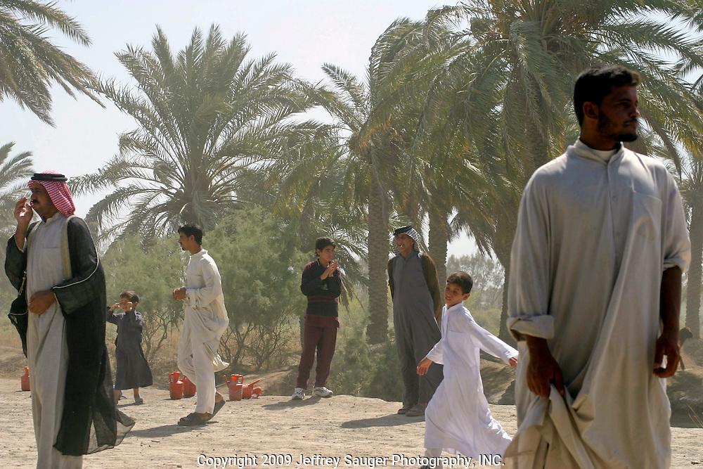 Strong winds kick up the sand during the Al-kasid family's Istikbal, or homecoming, in their home village Suq ash Shuyukh on the outskirts of Nasiriyah, Iraq, Wednesday, July 30, 2003. ..Young men and boys work throughout the 3 day celebration fetching water, serving food, cleaning, etc., which teaches them respect for their elders. In return, they are fed better than normal and get to be a part of the action as this was a huge event in the village. ..The Al-Kasid family fled Iraq after the Gulf War and their part in the uprising against Saddam Hussein in 1991, spent 3 years in Rafa, Saudi Arabia and finally settled in Dearborn, MI. The family hasn't been home to Iraq in 13 years...After the uprising in the Shiite dominated South, Saddam Hussein tried to kill the people by cutting off the rivers that village survival depends on. Dams and canals diverted the fresh water from flowing into the swamps by way of tributaries. In effect, without fresh water flowing in, the people started poisoning the water supply themselves by using it to wash and clean. Their primitive sewers still flow freely into the same waters that animals use and that feed their rice fields.