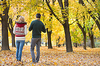 Rear view of young couple walking in park during autumn