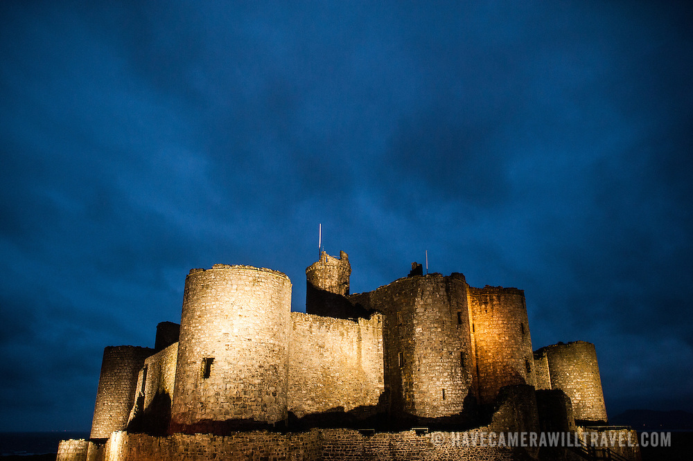 Night shot with dark blue overcast skies at Harlech Castle in Harlech, Gwynedd, on the northwest coast of Wales next to the Irish Sea. The castle was built by Edward I in the closing decades of the 13th century as one of several castles designed to consolidate his conquest of Wales.