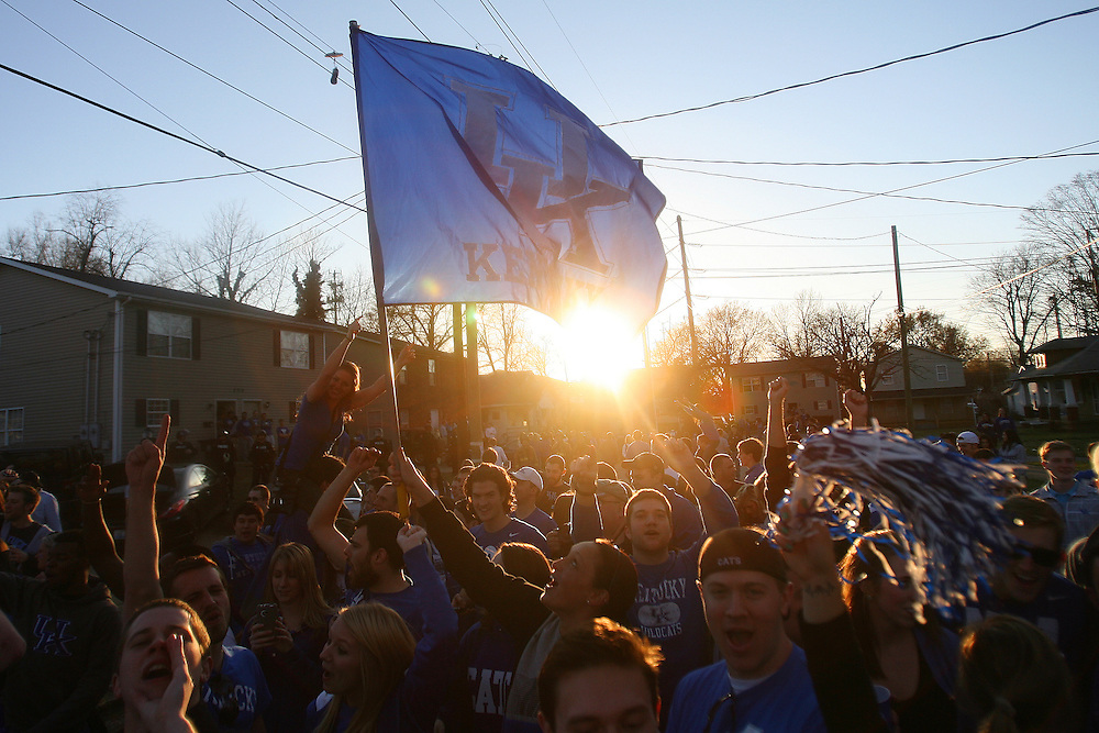 A Kentucky flag flies above Kentucky fans as they celebrate a victory that put Kentucky into the NCAA Final Four.