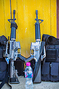 31 OCTOBER 2012 - YARANG, PATTANI, THAILAND:  Soldiers M16 rifles rest against a door in Wat Kohwai before soldiers escorted members of the temple to Yala for an Ok Phansa procession. Ok Phansa marks the end of the Buddhist 'Lent' and falls on the full moon of the eleventh lunar month (October). It's a day of joyful celebration and merit-making. For the members of Wat Kohwai, in Yarang District of Pattani, it was a even more special because it was the first time in eight years they've been able to celebrate Ok Phansa. The Buddhist community is surrounded by Muslim villages and it's been too dangerous to hold the boisterous celebration because of the Muslim insurgency that is very active in this area. This the year the Thai army sent a special group of soldiers to secure the village and accompany the villagers on their procession to Yala, a city  about 20 miles away.  PHOTO BY JACK KURTZ