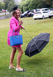 Not so Glorious Goodwood… A racegoer arriving at a wet and windy opening day of Glorious Goodwood in the UK, Tuesday, 30th July 2013 <br /> Picture by Stephen Lock / i-Images