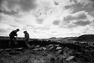 Men cutting peat on a stretch of land on the island of Lewis in the Outer Hebrides, Scotland. Peat cutting was a traditional method of gathering fuel for the winter in the sparsely-populated areas on Scotland's west coast and islands. The peat was dried and used in fires and ovens.
