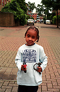 Cheeky young boy with toy gun and handcuffs, Lambeth Walk, South London, 2000's