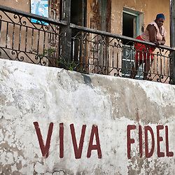 Woman on the balcony with a painting on the wall supporting Fidel Castro. Santiago de Cuba, Cuba, Caribbean.