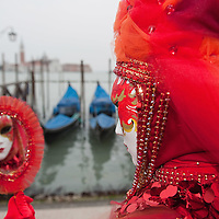 VENICE, ITALY - FEBRUARY 11:  A  woman wearing Carnival costume poses for pictures in front of the gondolas in St Mark's Square on February 11, 2012 in Venice, Italy.The annual festival, which lasts nearly three weeks, will see the streets and canals of Venice filled with people wearing highly-decorative and imaginative carnival costumes and masks.