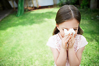Little girl in backyard blowing nose close up