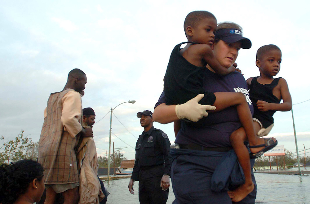 (8/29/2005). EMT Stacey Becker, 27, carries twins DeShane and Dennis Sims, 4, after they were rescued from the Lower 9th Ward District of New Orleans after of Hurricane Katrina landed.(Times photo by Willie J. Allen Jr.).