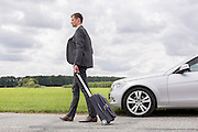 Full length of young businessman with suitcase walking by broken down car at countryside