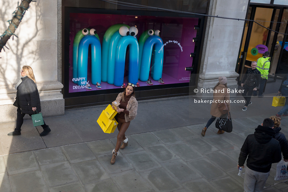 Carrying three yellow branded shopping bags, a lady emerges the Selfridges department store on London's Oxford Street, and passes by a themed window display that includes some cartoon-esque characters wishing the public a happy new decade, on 7th February 2020, in London, England.