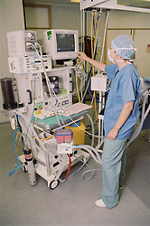 Anaesthetist at work adjusting monitor during operation in hospital theatre,