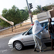 February 2008 - An African blind woman and his son beg for money in the traffic jam in the streets of Cotonou, Benin.