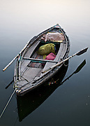 A wooden boat rests in tranquility along the Ganges River in Varanasi, India.