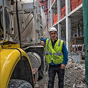 Construction worker standing next to concrete pump truck, concrete being pumped up to top floor of building  at 192 7th Avenue, NYC.