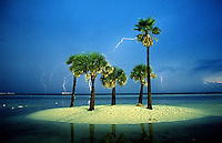 Lighting strikes the Gulf of Mexico as scene from Clearwater Beach FL. Heavy rains cause the water to pool on the beach crating an island.