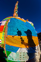 The shadow of a Tibetan pilgrim spinning a prayer wheel as he circumambulates around The Barkhor, Lhasa, Tibet, China.