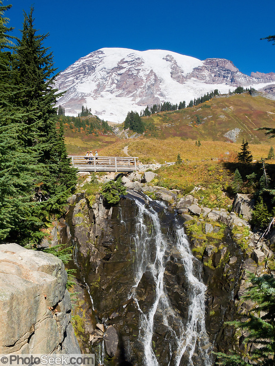 Myrtle Falls. Three women hikers explore fall foliage colors in Paradise Valley in Mount Rainier National Park, Washington, USA. Skyline Trail is one of the great day hikes of the world. Mount Rainier rises to 14,411 feet elevation.