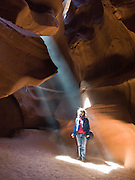 """A ray of sunlight pierces the sandstone slot of Upper Antelope Canyon, in Antelope Canyon Navajo Tribal Park, Page, Arizona, USA. . (The older spelling """"Navaho"""" is no longer used by the Navajo, an American Indian group who call themselves Diné, or Dineh, """"The People."""") For licensing options, please inquire."""