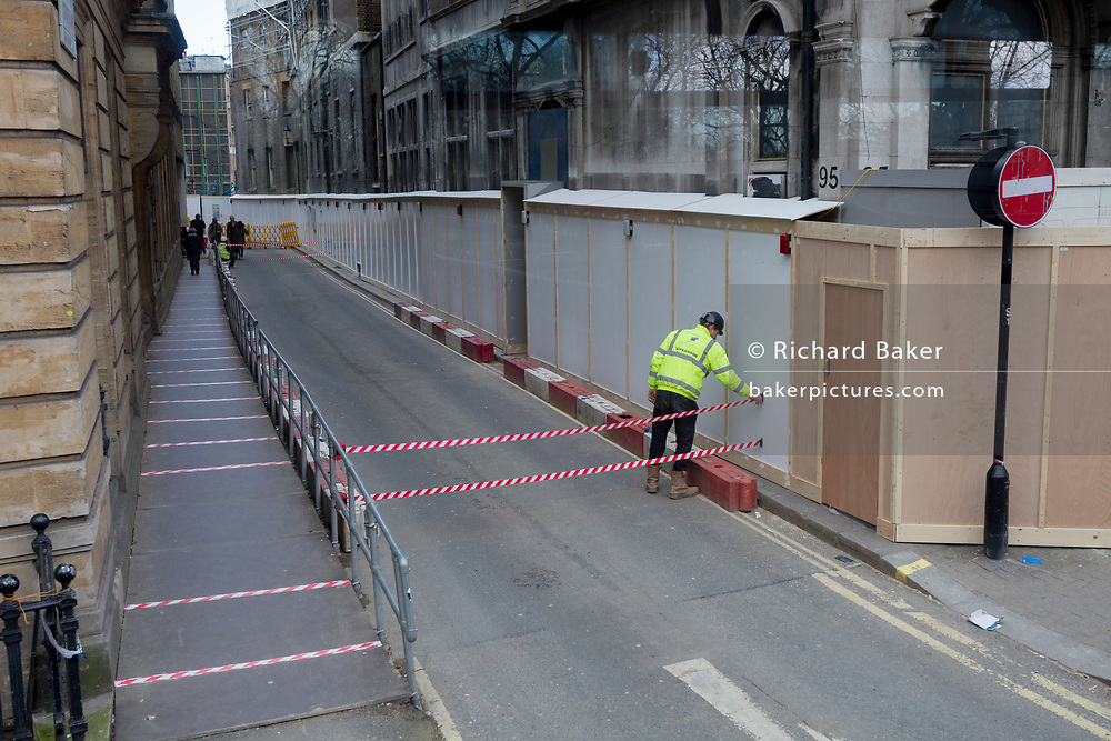 A workman on a Mayfair construction project secures the tape stretching across a side-street blocked off to normal traffic off Piccadilly, on 12th March 2020, in London, England.