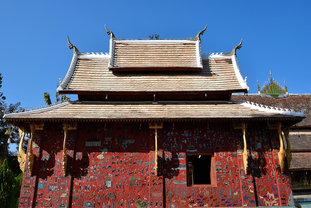 The Red Chapel at Wat Xieng Thong in Luang Prabang, Laos <br /> The Red Chapel at Wat Xieng Thong is one of the most unusual that I have seen at a temple or wat in Southeast Asia.  Its red stucco façade is covered with glass mosaics that illustrate the religious and everyday activities of Laotians.  They were added in 1957 to celebrate the 2,500th anniversary of the Buddha's death.  Inside is a 16th century reclining Buddha that represents his achievement of Nirvana.