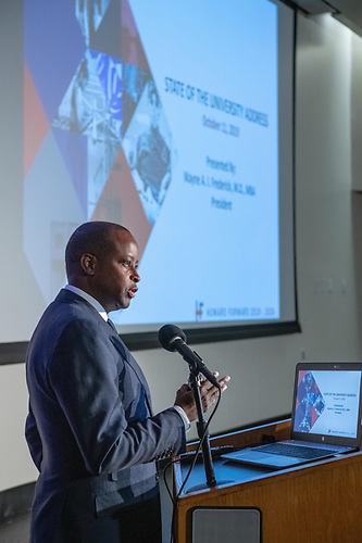 Howard University President Wayne A. I. Frederick presents the State of the University address in front of a projector.