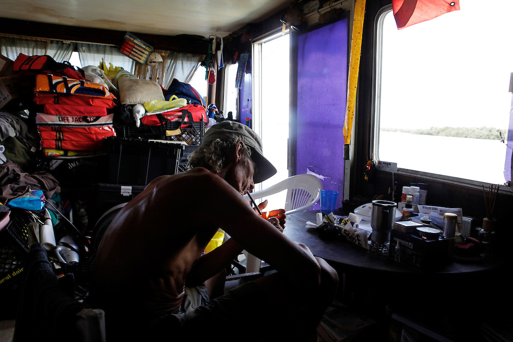 "Scot Janikula, 50, has a seat in his houseboat after getting back from running errands in town. Janikula, has been living on a boat in Estero Bay for 13 years. Janikula says part of the attraction of living on a boat is that he doesn't have almost any bills to pay. ""You can't do anything on land without it costing money,"" Janikula said."