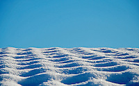 Snow-covered roof against a clear, blue sky forms a brilliant, white, crystalline  pattern.