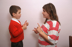 Two young children with hearing impairments using sign language to communicate with each other,